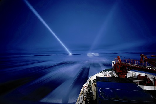 B0XY5A icebreaker in Antarctica during night with a research vessel, with bright light beams searching for dangerous icebergs, Antarct