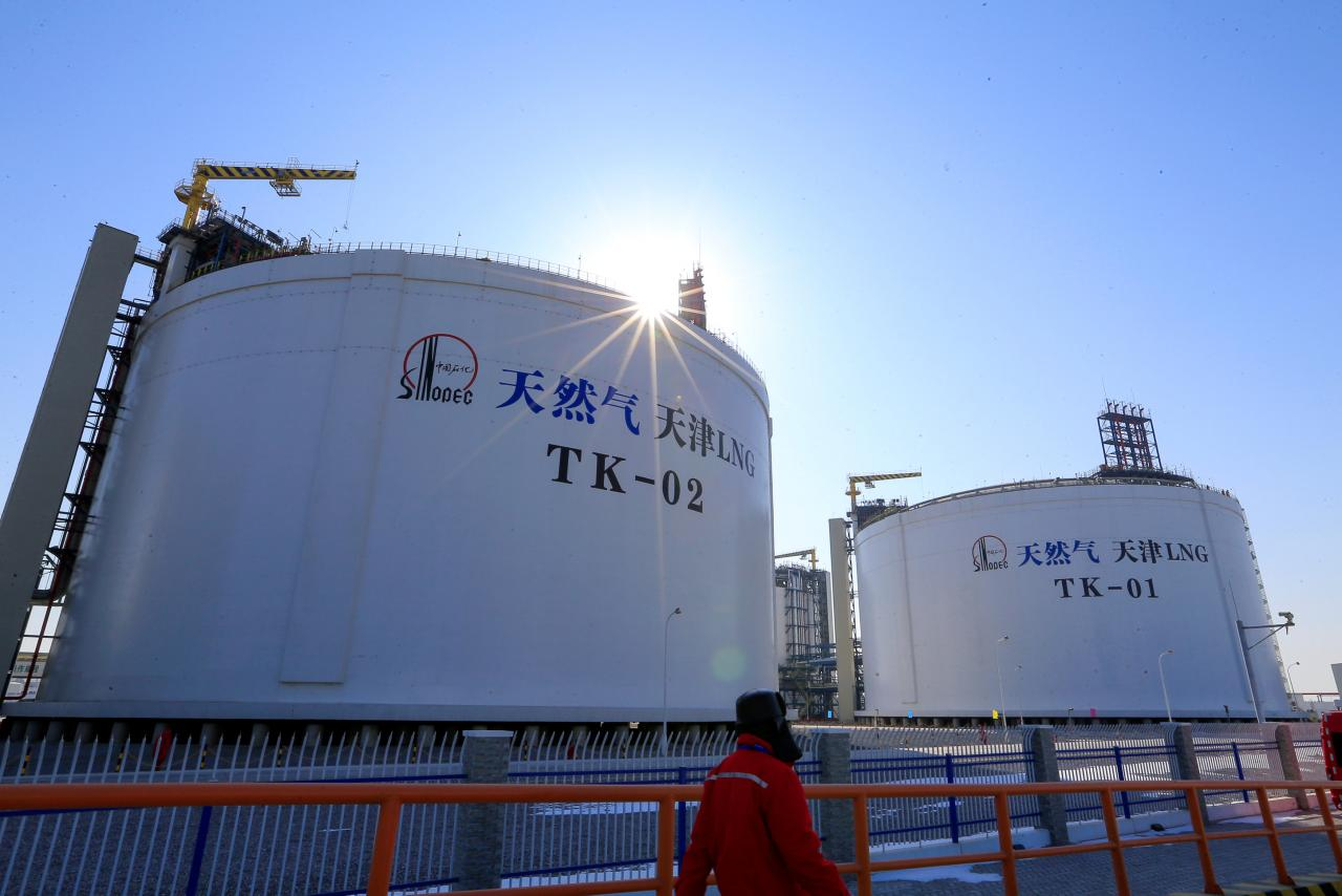 FILE PHOTO: A Sinopec worker walks past liquified natural gas (LNG) storage tanks at Sinopec's LNG terminal in Tianjin, China February 6, 2018. REUTERS/Stringer/File Photo
