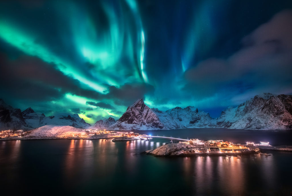 Aurora borealis. Lofoten islands, Norway. Aurora. Green northern lights. Starry sky with polar lights. Night winter landscape with aurora, sea with sky reflection and snowy mountains.